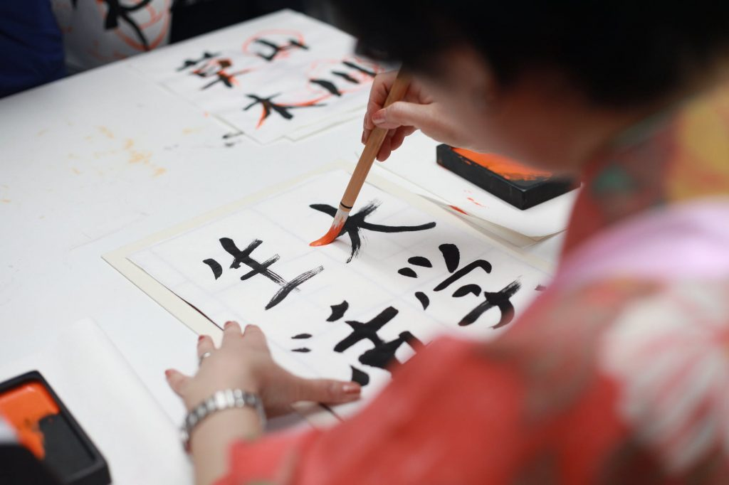 Translating to Japanese is complex one reason being that Japanese has three character sets. Image shows a Japanese girl writing in kanji script.